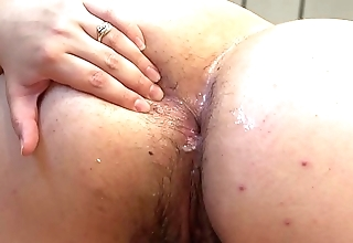 A big unfocused stuffs cucumbers into her ass.
